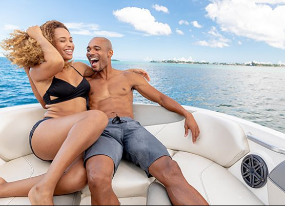 a man and woman sitting on the front of a boat laughing
