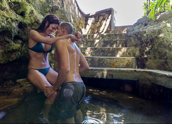 a man and woman with their arms around each other in a secluded tub surrounded by rocks