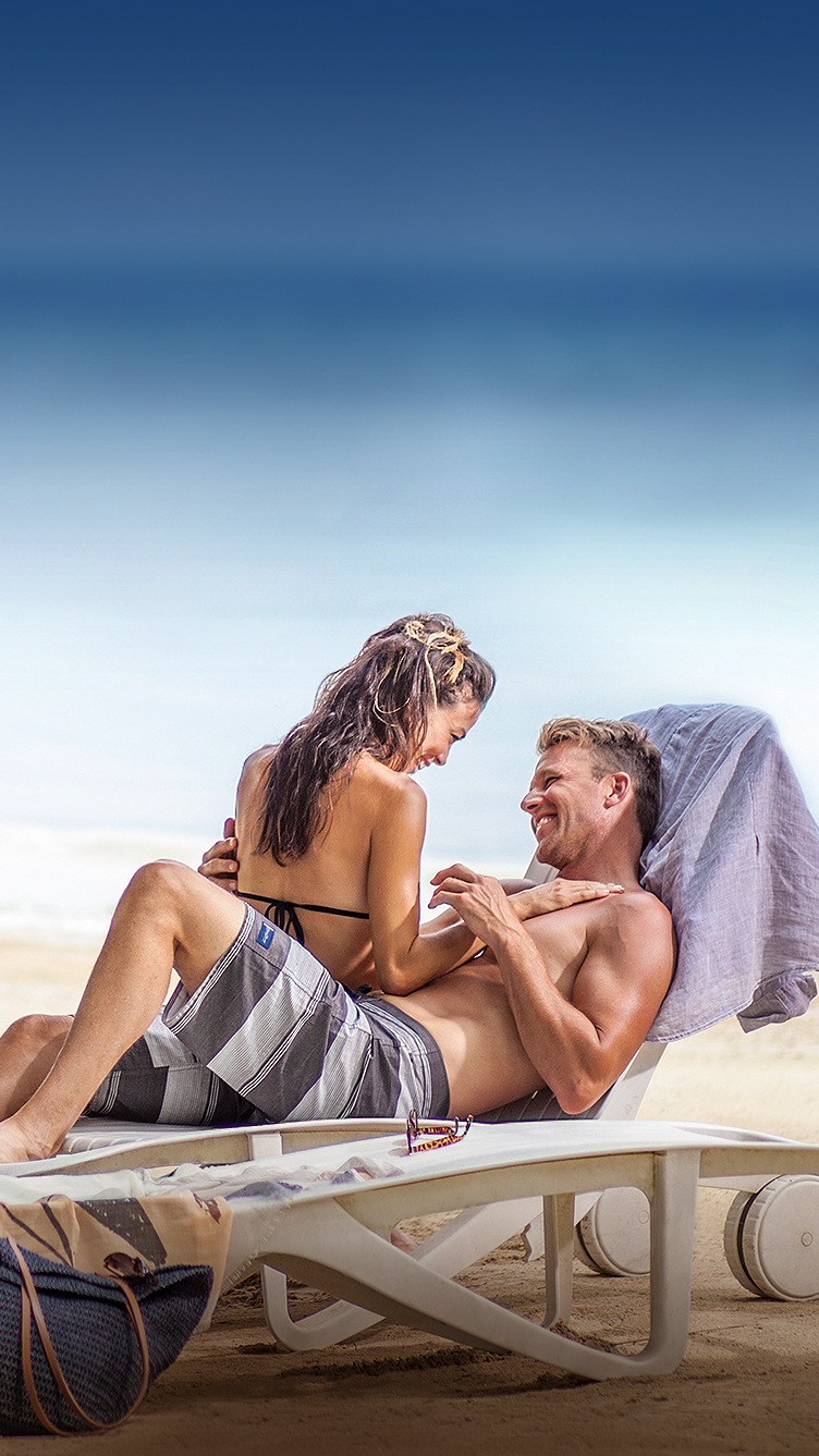 man and woman sitting together on a lounge chair on the beach