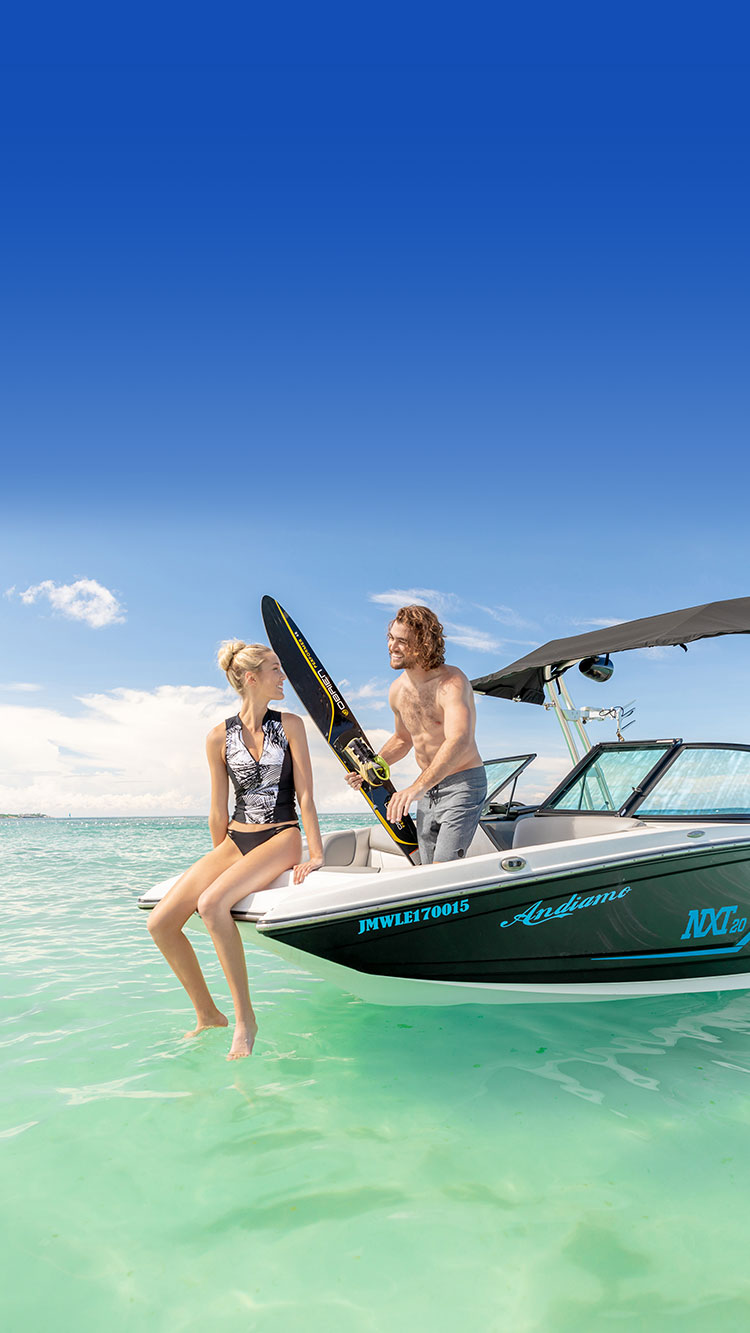 couple sitting on the front of a sport boat about to get in the water and go skiing