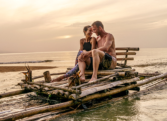 couple sitting on a bamboo raft in the water at sunset
