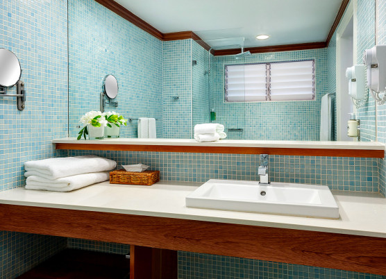 bathroom vanity area with blue tile walls, wooden shelving, and a large mirror