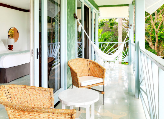 guest room balcony with wicker chairs, small side table, and a hammock