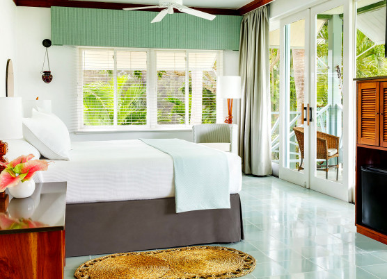 guest bedroom with white linens, light blue quilt at end of bed, blue tile floors, wooden furniture, and double doors leading to a balcony