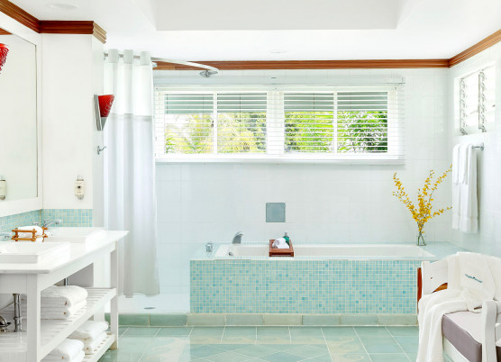 bathroom area with a tub, walk in shower, bench, and vanity with shelving underneath