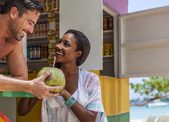 couple at an outdoor beach bar drinking out of a coconut