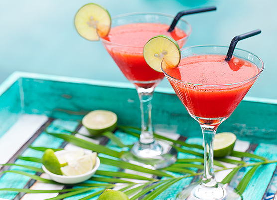 two red cocktail drinks in a martini glass with a lime slice on the rim