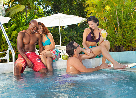 two couples sitting by the hot tub enjoying drinks