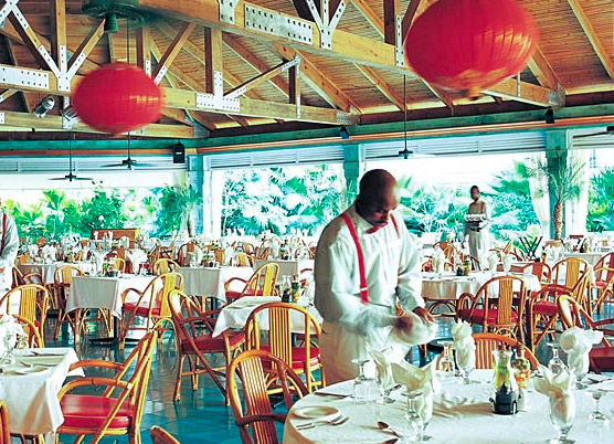 a waiter preparing table settings for dinner at a covered outdoor restaurant