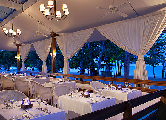 elegant covered outdoor dining area with white drapes, white tablecloths, and a view of the beach and ocean