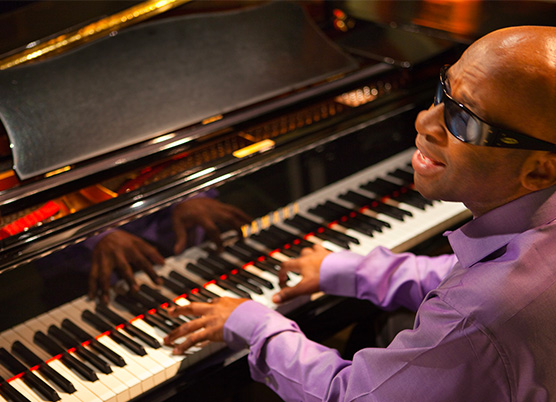 a man wearing sunglasses playing the piano