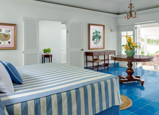 hibiscus cottage bedroom with striped bedspread and blue tile floors