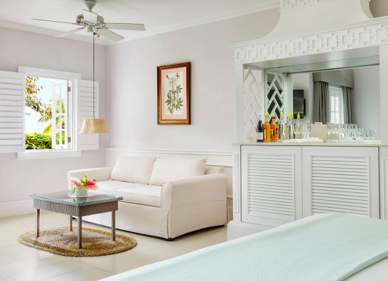 one bedroom beachfront suite living room with light colored beach inspired furniture