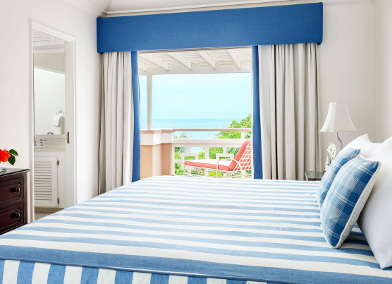 penthouse suite with blue and white striped furniture with balcony window overlooking the ocean