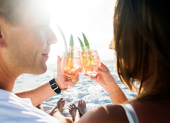 couple clinking drinks together on a beach