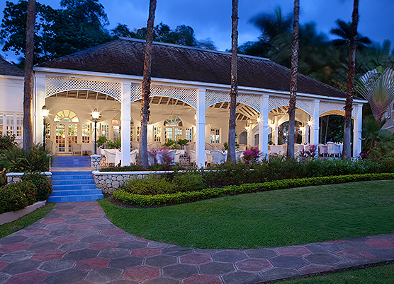 long white gazebo with dining tables set up underneath at night