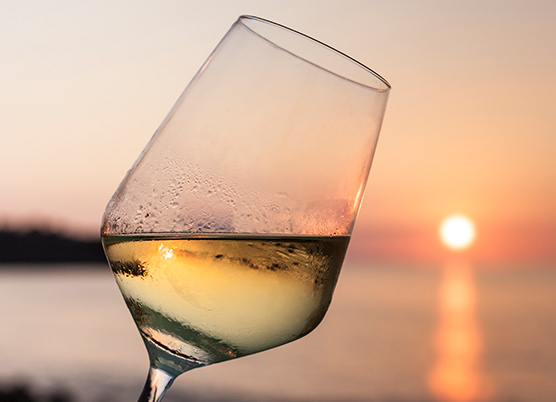 white wine in a glass overlooking sunset