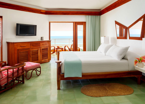 a guest room with white bed linens and a beach view from the balcony