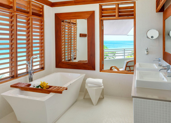 a bathroom with large white soaking tub and beach views