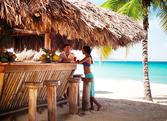 couple having drinks at the bamboo bar on the beach