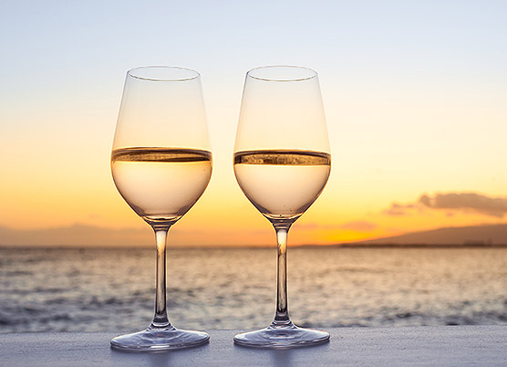 two glasses of white wine on a ledge in front of the ocean at sunset