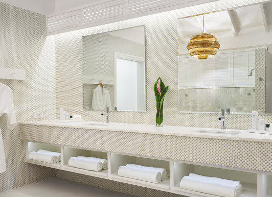 bathroom area with a double sink vanity, shelving underneath with rolled up towels, robes hanging, and two mirrors