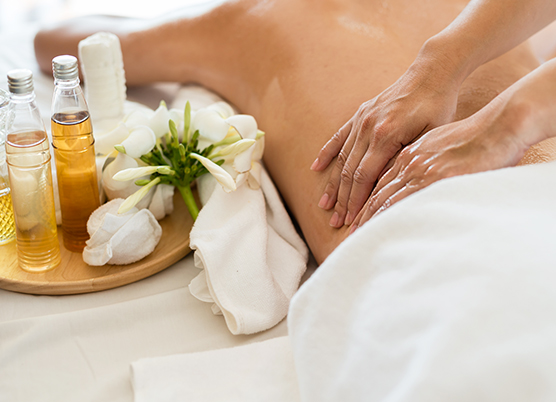 woman getting a back massage at the spa with a tray of spa treatments on the bed