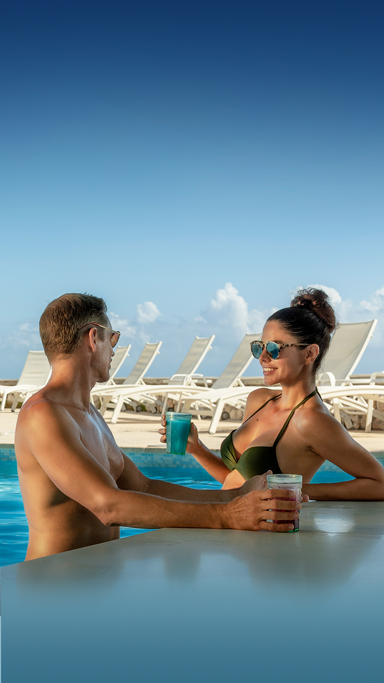 couple having drinks at a swim up pool bar