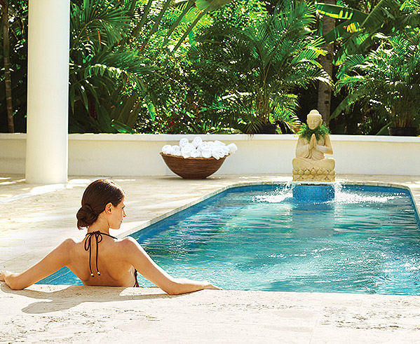 woman sitting in a small pool with a buddha fountain
