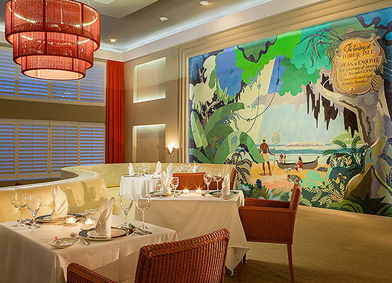 fine dining restaurant set for dinner with a colorful mural on wall