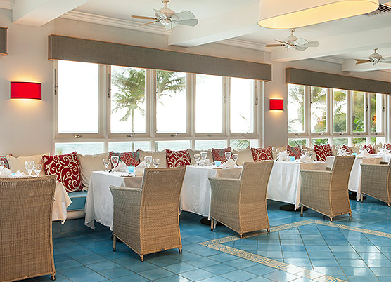 indoor restaurant dining area with bench seating and tan wicker chairs overlooking the ocean