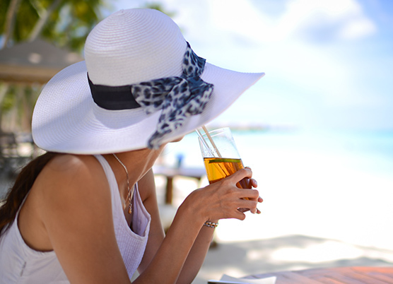 woman sipping tea wearing a white wide brim hat on the beach