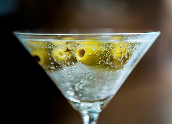 close up of a martini filled with green olives