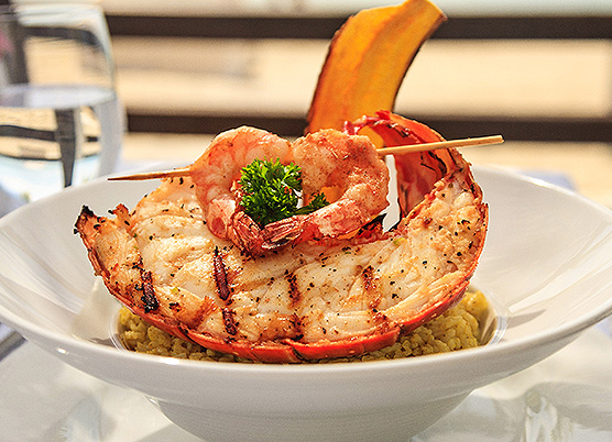 lobster topped with shrimp overtop a bowl of rice