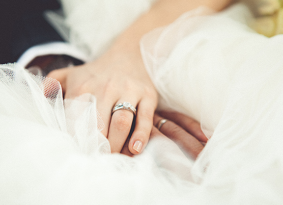 close up of a bride and grooms hands laying on the brides gress