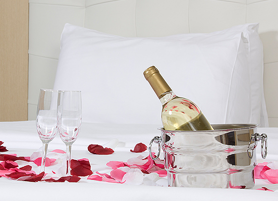 wine bottle sitting in a metal ice bucket on a bed with two glasses and rose petals on bed