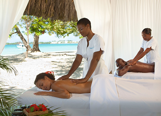a couple getting a couples massages at an outdoor spa covered with white curtains