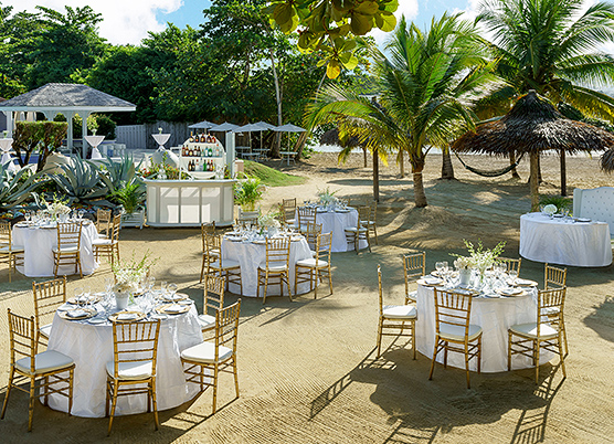 wedding reception tables on the sand with gold chairs and white tablecloths