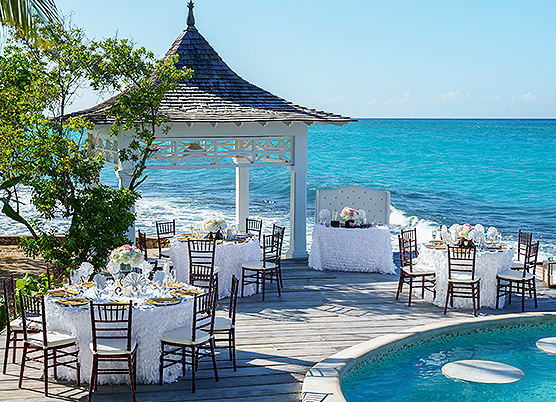 round tables with white table cloths on a terrace with a gazebo and pool overlooking the ocean