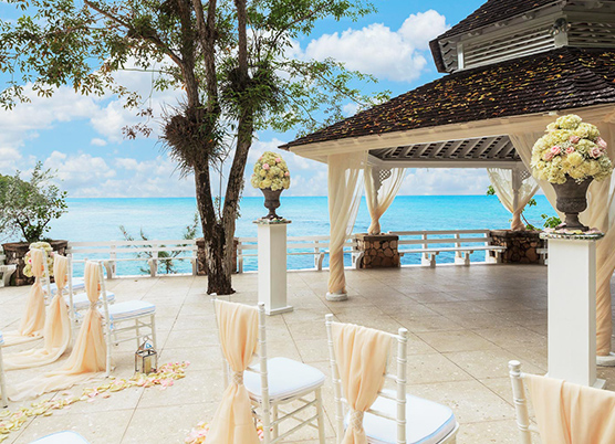 wedding ceremony set up on a terrace with a gazebo overlooking the ocean