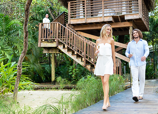 couple walking on a boardwalk away from a treehouse