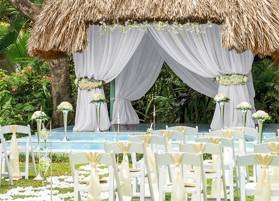 wedding ceremony set up at a tiki hut with white drapes hanging to the side