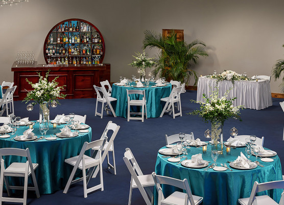indoor event space area with blue tablecloth round tables, white folding chairs, and flower table centerpieces