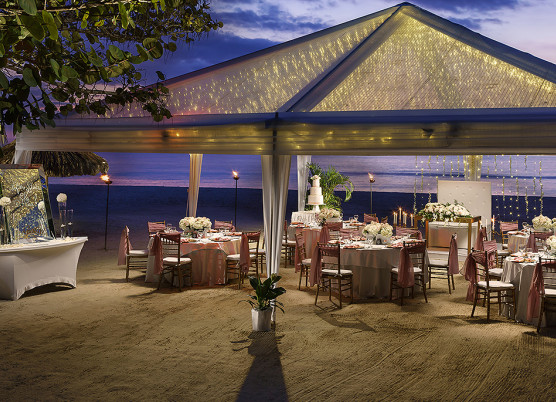 a wedding dining reception on the beach at night covered with a large tent