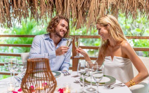 couple having dinner on a balcony underneath a tiki hut