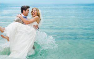 groom holding the bride as he walks through the ocean water