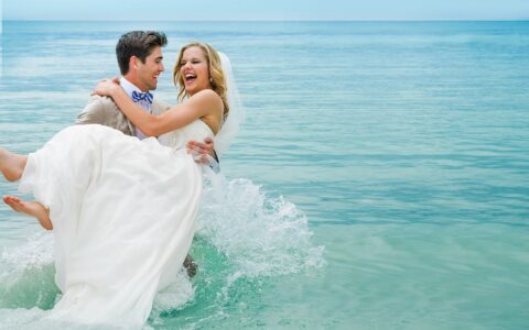 groom holding the bride as he walks through the ocean water