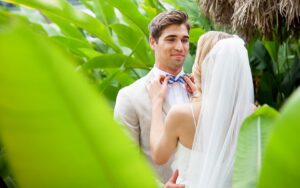 bride adjusting the groom's bowtie seen from behind a palm leaf