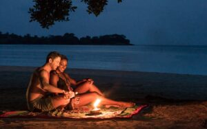 couple sitting on a blanket with a candle having drinks on the beach at night