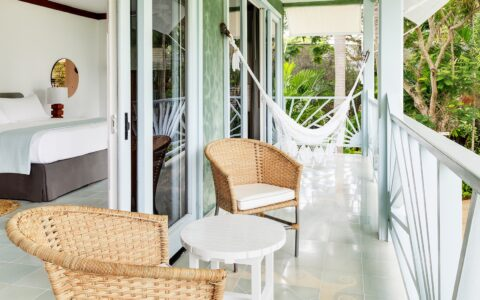 patio chairs and a hammock on a balcony outside a guest bedroom